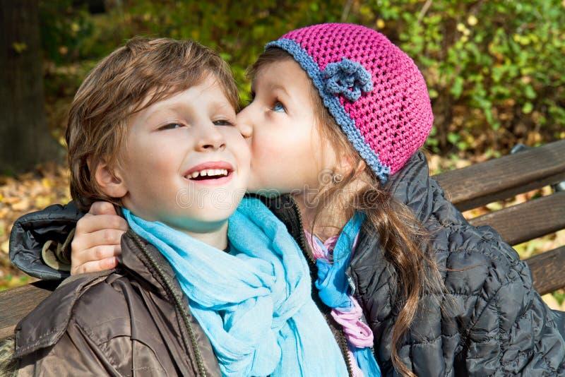 Menina que beija um menino em um banco fotos de stock royalty free
