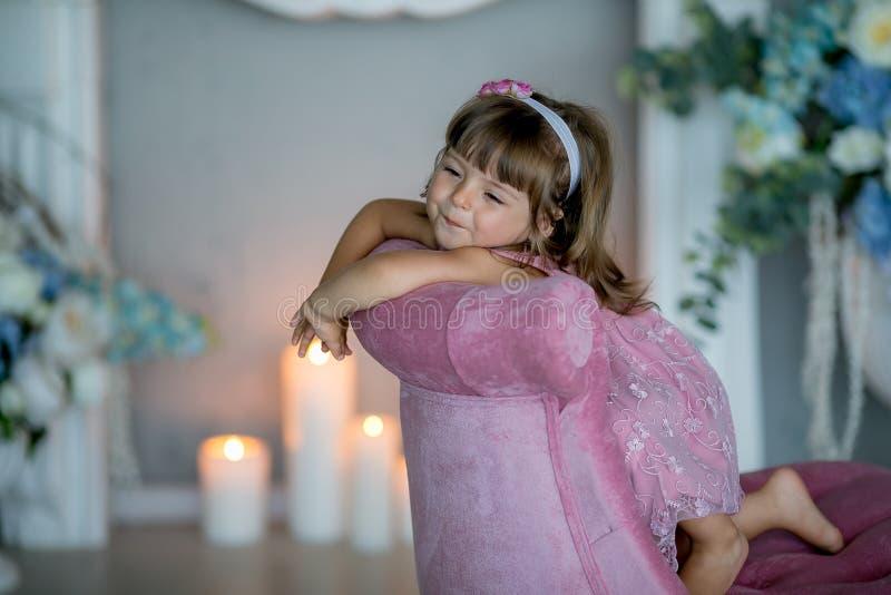 A menina que bonita nova a bailarina em um vestido cor-de-rosa branco está estando em uma sala branca perto de uma tabela branca  imagens de stock royalty free
