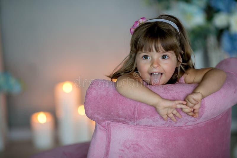 A menina que bonita nova a bailarina em um vestido cor-de-rosa branco está estando em uma sala branca perto de uma tabela branca  fotografia de stock