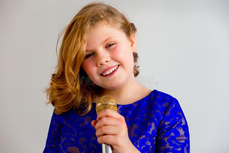 Menina que canta com um microfone foto de stock royalty free