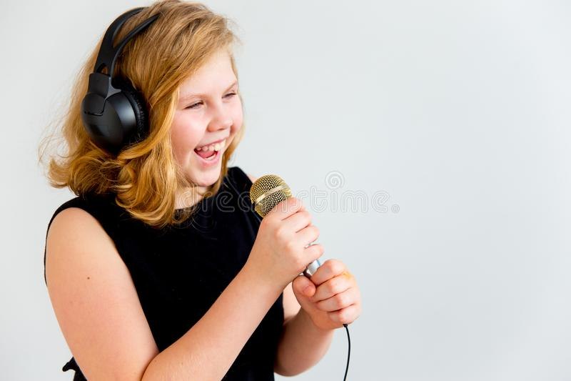 Menina que canta com um microfone fotos de stock royalty free