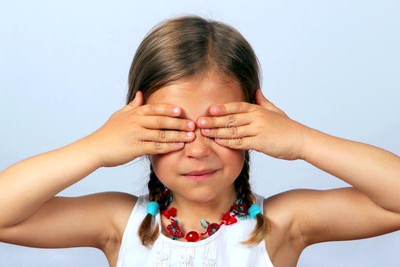 Menina que cobre seus olhos imagem de stock