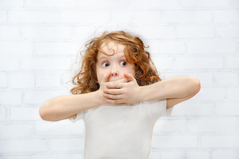 Menina que cobre sua boca com suas mãos Surpreendido ou cicatriz fotografia de stock