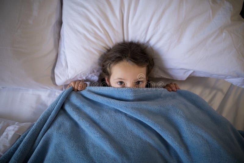 Menina que cobre sua cara sob a cobertura ao encontrar-se na cama imagem de stock