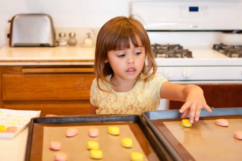 Menina que coloca a massa da cookie na folha de cookie foto de stock