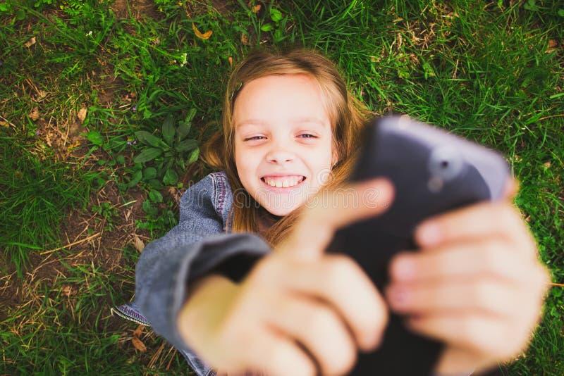 Menina que coloca na grama com telefone celular imagens de stock