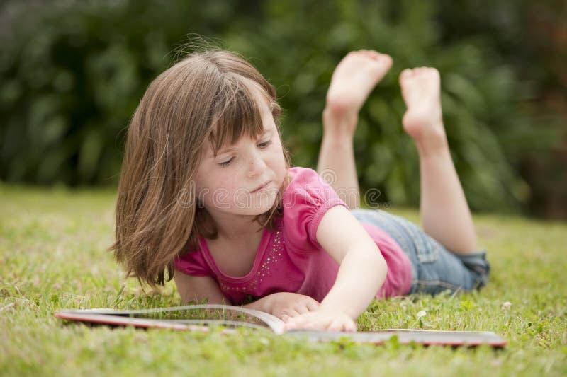 Menina que coloca na leitura da grama foto de stock