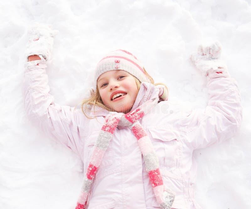 Menina que coloca no anjo de factura à terra da neve fotografia de stock