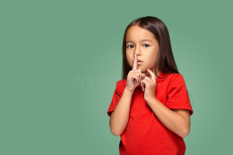 Menina que coloca o dedo nos bordos que pedem shh, silêncio, silêncio imagem de stock royalty free
