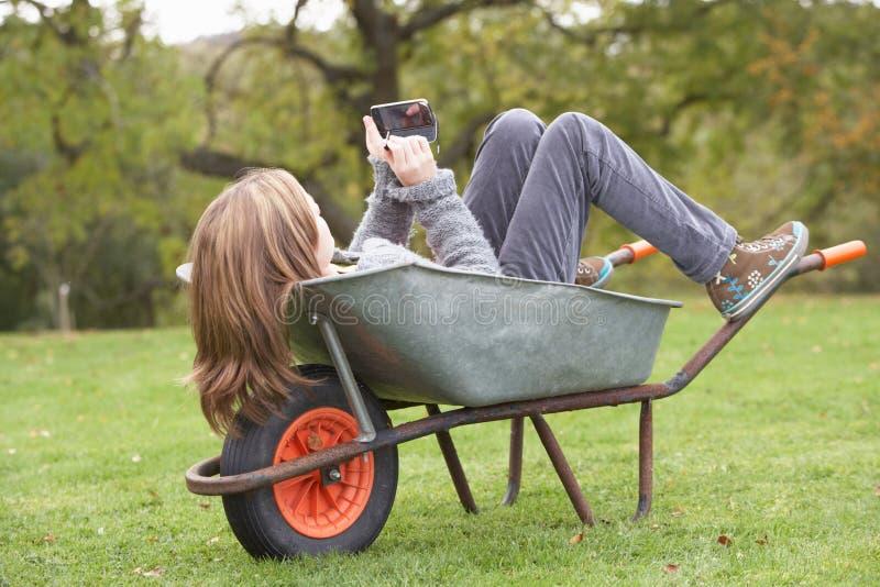 Menina que coloca o Wheelbarrow usando o telefone esperto imagem de stock
