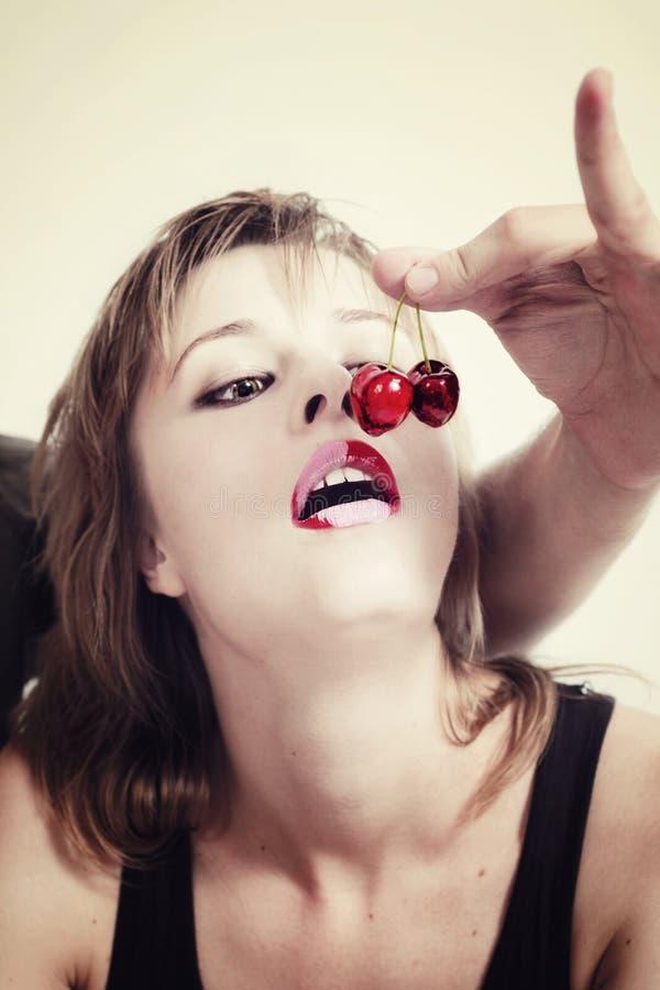 Menina que come cerejas fotografia de stock royalty free