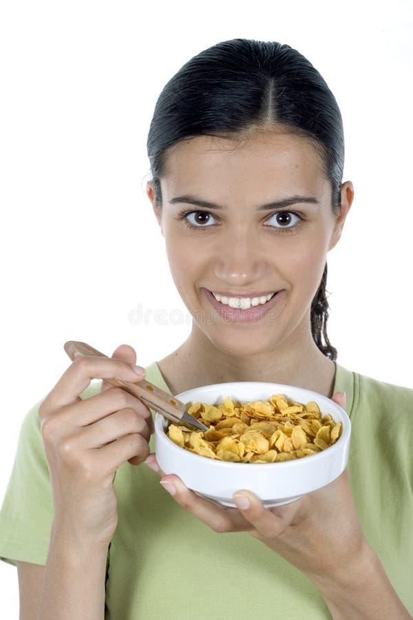 Menina que come cornflakes fotografia de stock