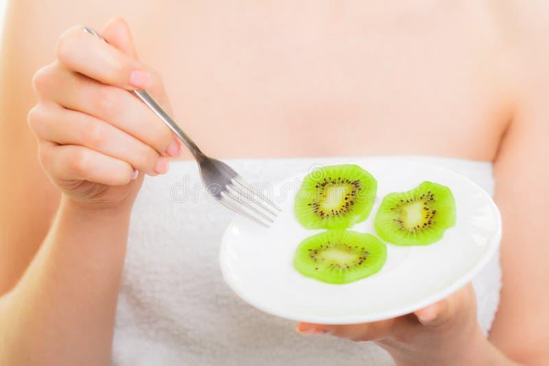Menina que come fatias de fruto de quivi Dieta saudável fotos de stock royalty free