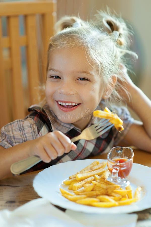 Menina que come fritadas do francês imagens de stock