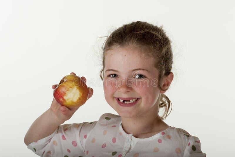 Menina que come a maçã vermelha imagem de stock