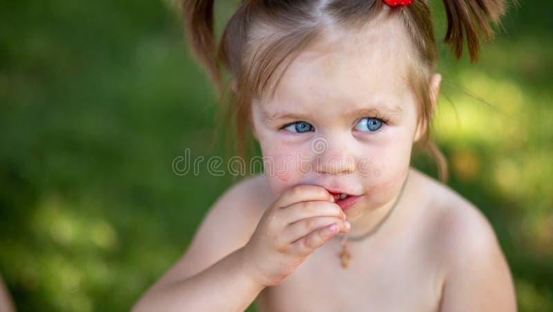 Menina que come a melancia fim manchado acima do retrato de uma menina loura nova com melancia, verão Healt exterior da boca imagens de stock royalty free