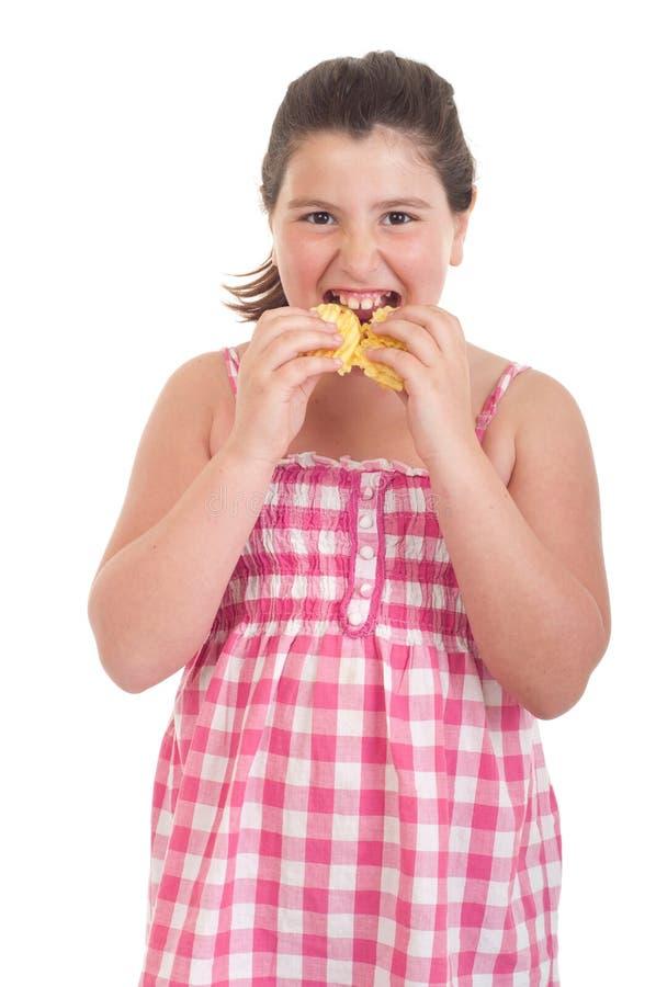 Menina que come microplaquetas foto de stock royalty free