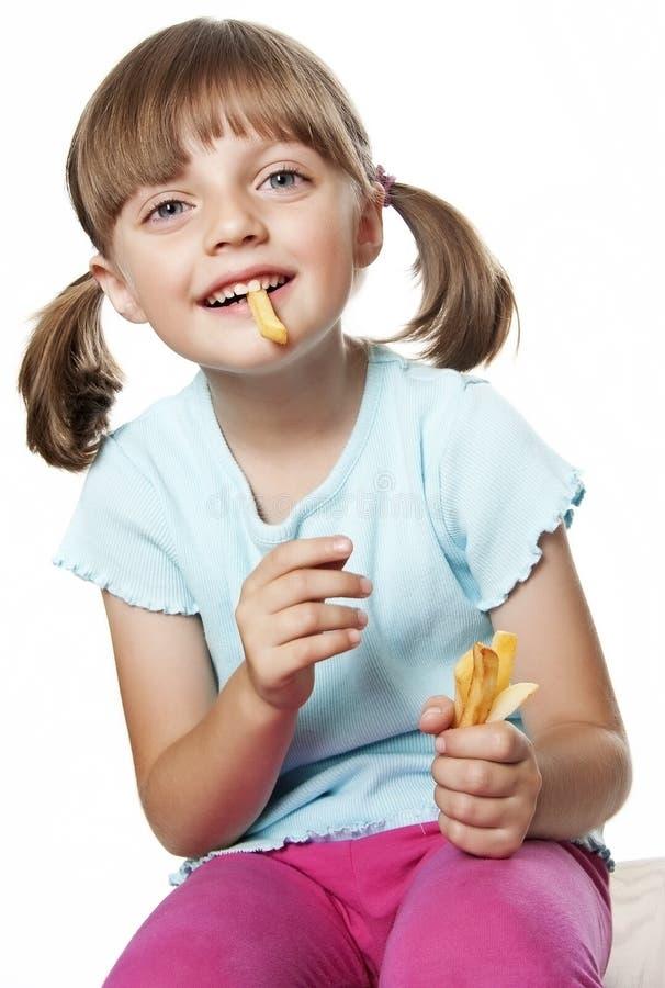 Menina que come microplaquetas de batata foto de stock royalty free