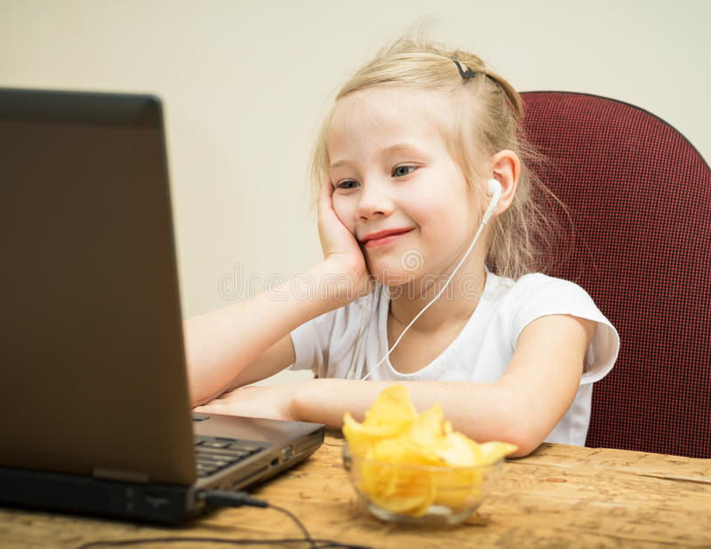 Menina que come microplaquetas de batata do portátil imagens de stock