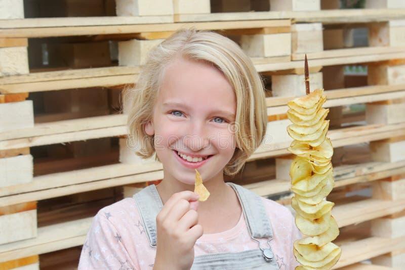 Menina que come microplaquetas de batata em uma vara Comida lixo, alimento da rua, petisco em uma caminhada imagem de stock royalty free