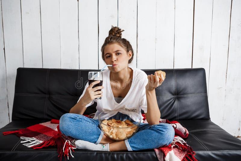 Menina que come microplaquetas, soda bebendo, tevê de observação, sentando-se no sofá fotografia de stock royalty free