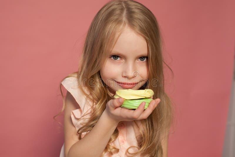 Menina que come o bolo com o doce de creme do queque imagens de stock royalty free