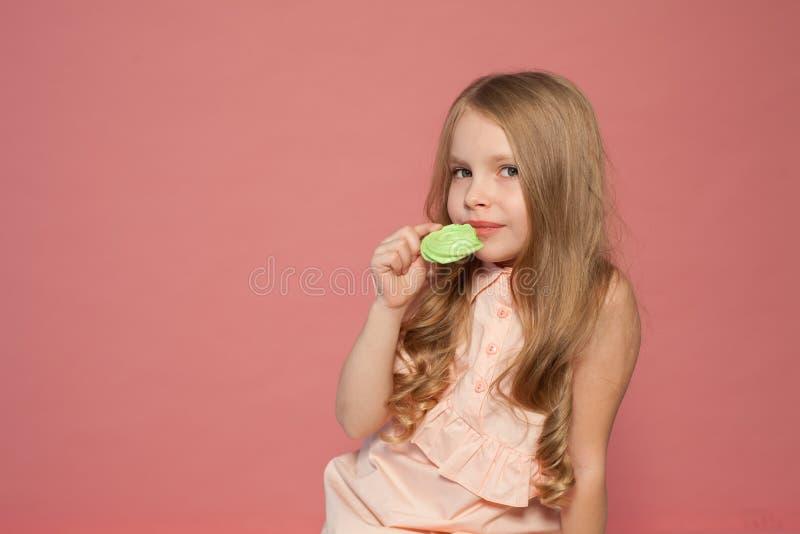 Menina que come o bolo com o doce de creme do queque fotos de stock