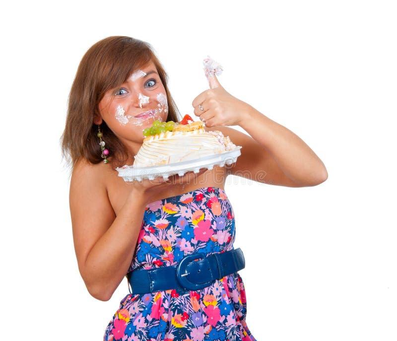 Menina que come o bolo com suas mãos fotografia de stock royalty free