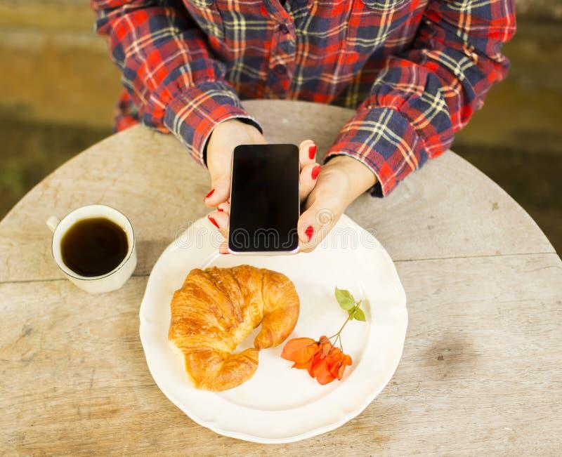 Menina que come o café da manhã e que usa o telefone celular imagens de stock