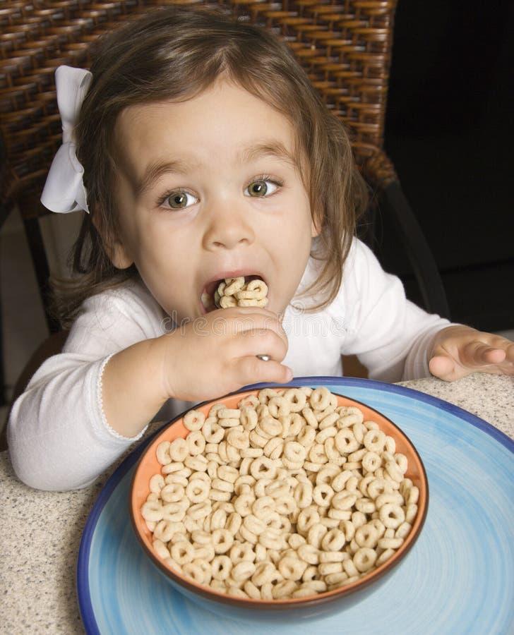 Menina que come o cereal. fotos de stock royalty free