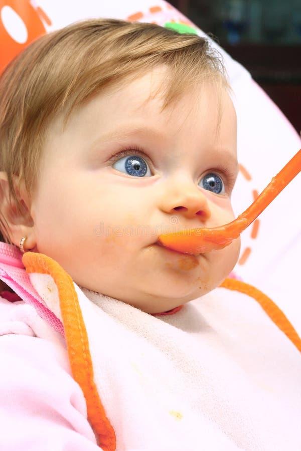 Menina que come o comida para bebé fotos de stock royalty free