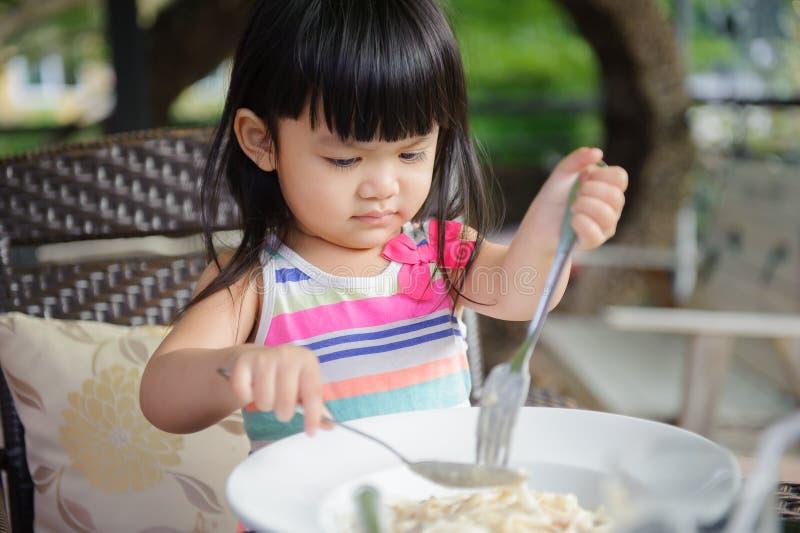 Menina que come o espaguete imagens de stock