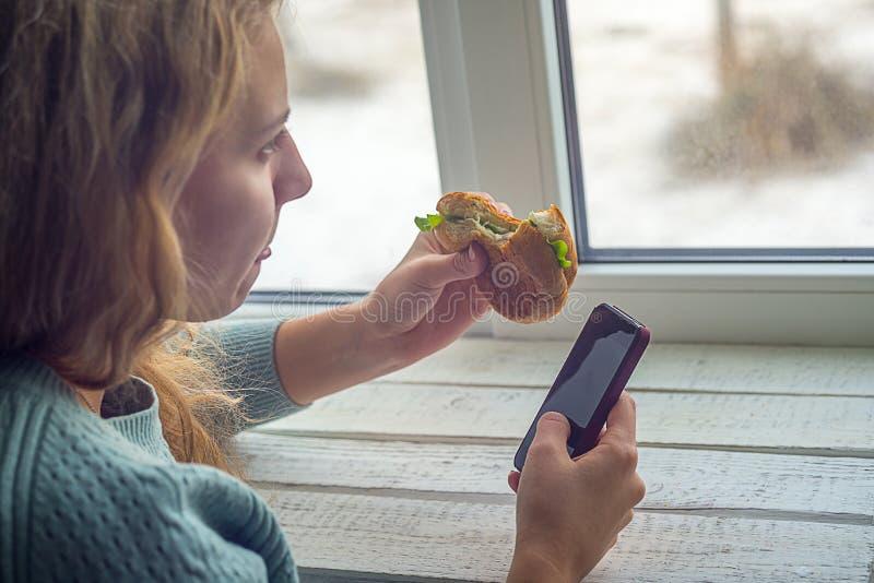 Menina que come o hamburguer e que olha o telefone imagens de stock