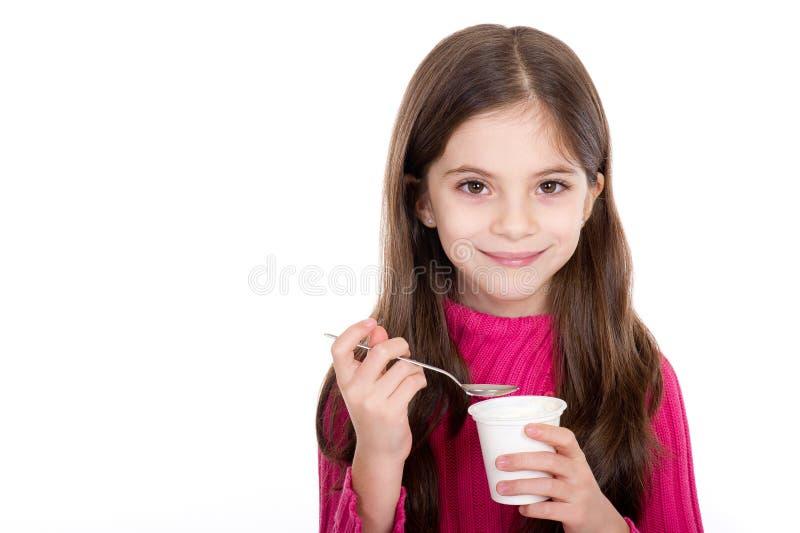 Menina que come o iogurte fotografia de stock royalty free