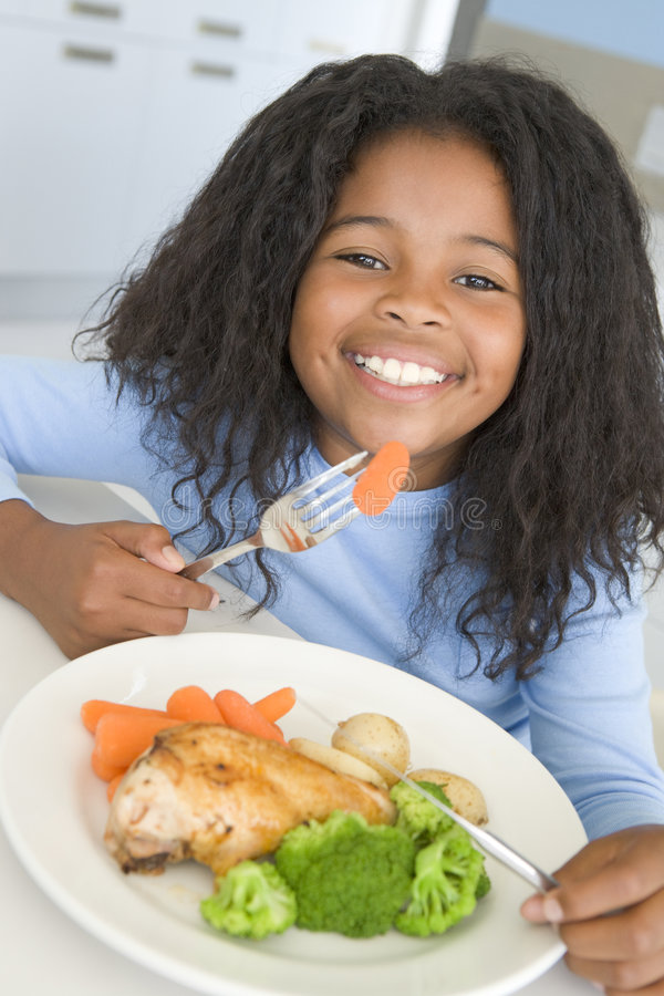 Menina que come o jantar da galinha e do vegetal em casa foto de stock