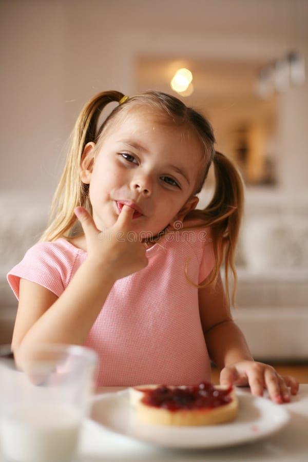 Menina que come o pequeno almoço foto de stock
