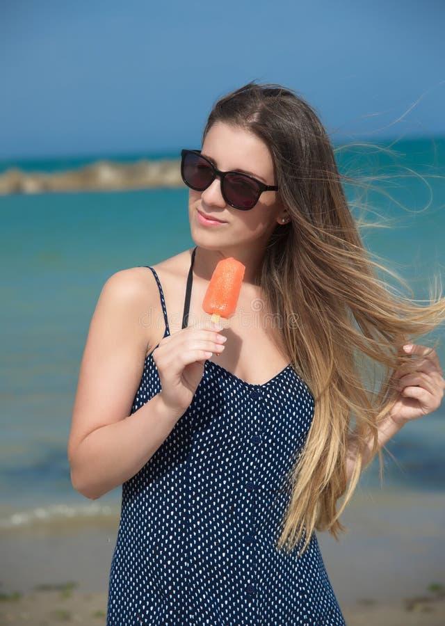 Menina que come o picolé na praia fotografia de stock royalty free