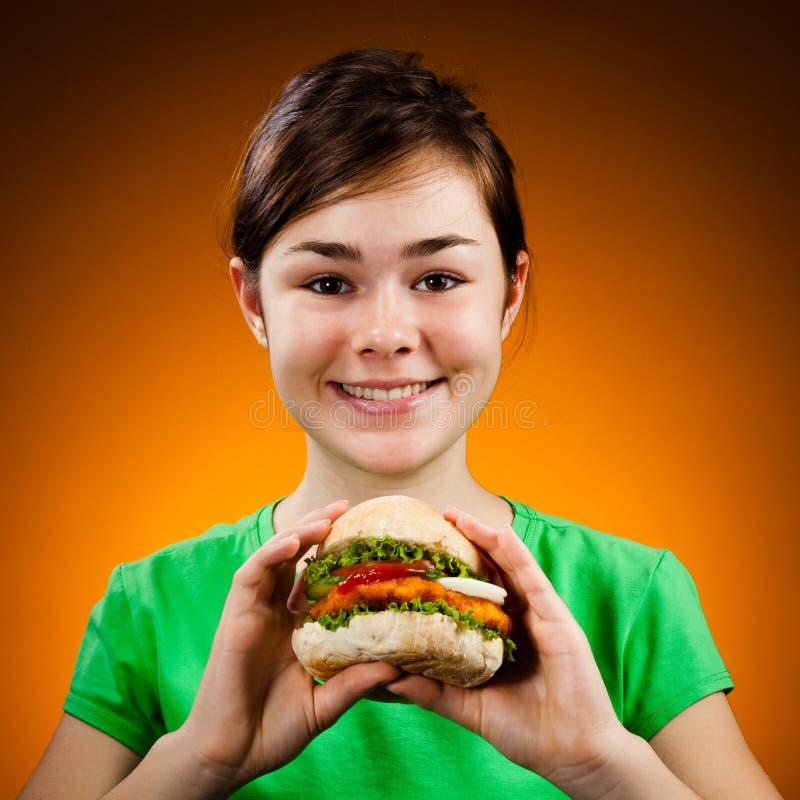 Menina que come o sanduíche grande fotografia de stock royalty free