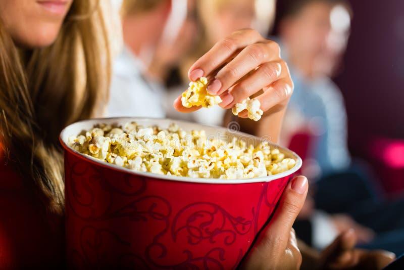 Menina que come a pipoca no cinema ou no cinema imagens de stock royalty free