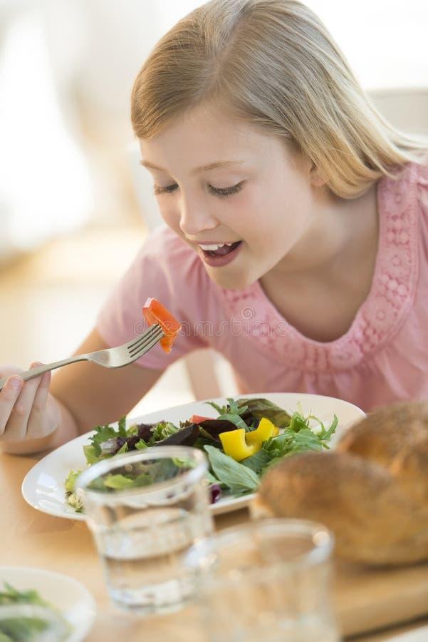 Menina que come a salada na mesa de jantar foto de stock royalty free
