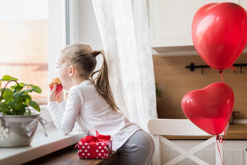 Menina que come seu queque do aniversário na cozinha, cercada por balões foto de stock