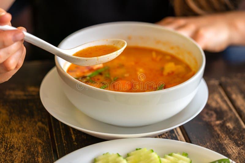 Menina que come Tom Yam Kung, culinária tailandesa Fim acima fotos de stock royalty free
