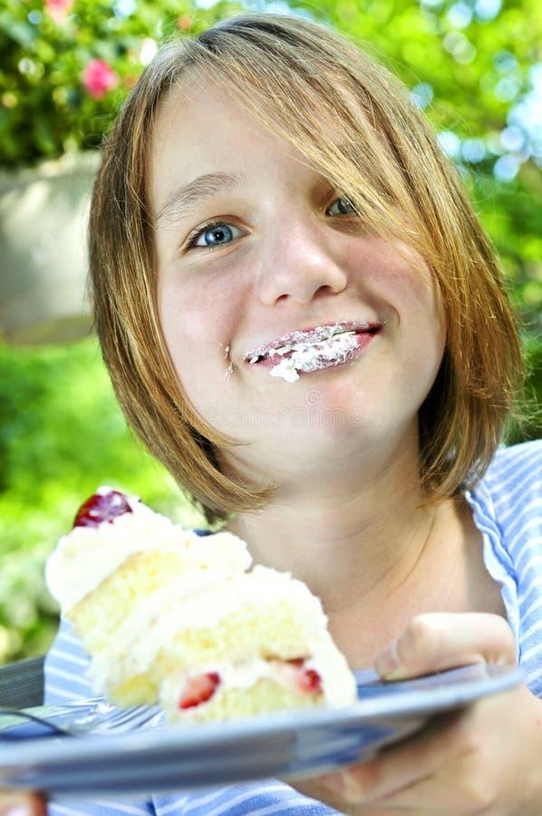 Menina que come um bolo foto de stock royalty free