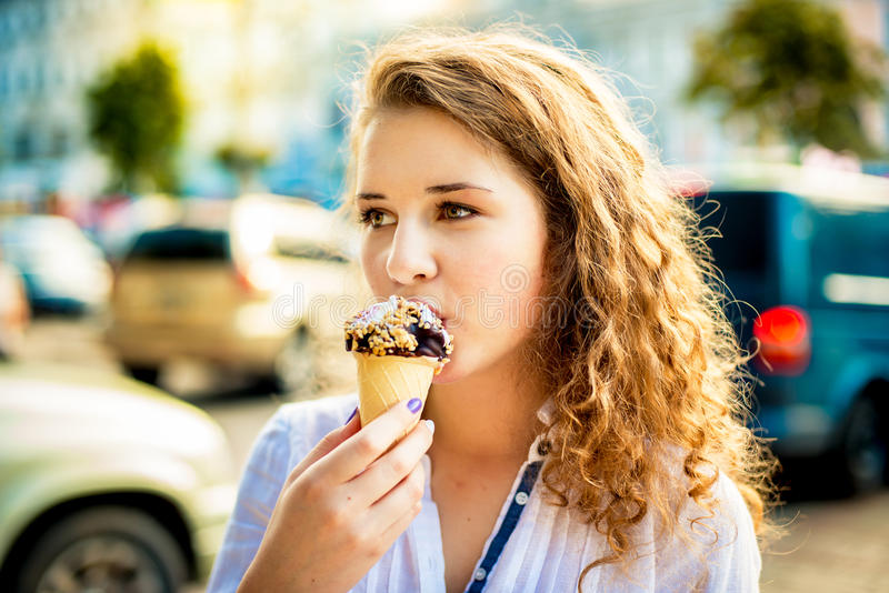 Menina que come um gelado delicioso de chocolate fotografia de stock royalty free