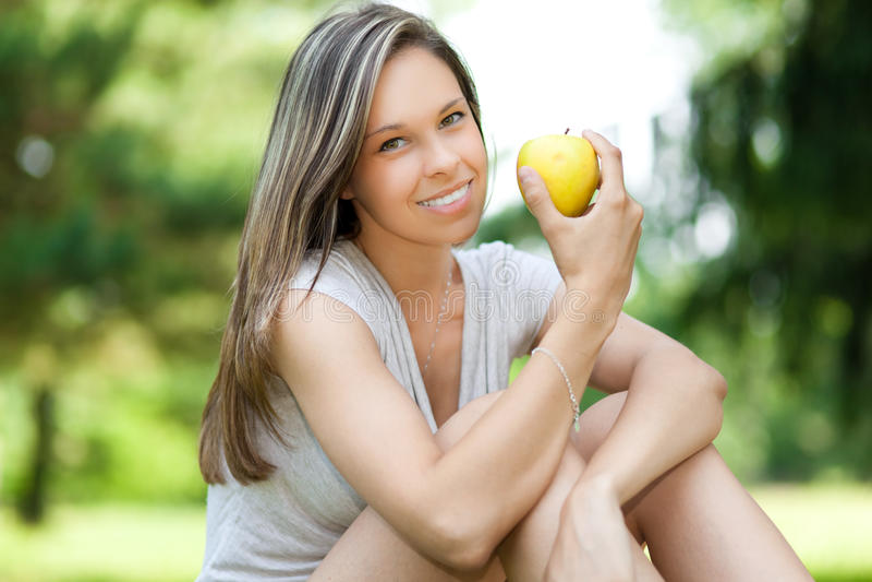 Menina que come um petisco saudável da maçã imagem de stock
