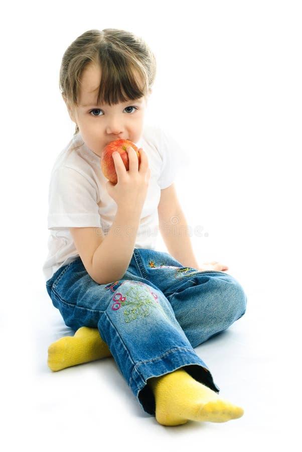 Menina que come uma maçã foto de stock royalty free