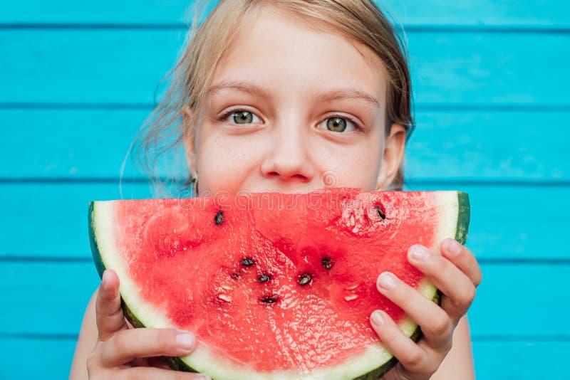 Menina que come uma melancia suculenta madura sobre a parede azul da prancha foto de stock royalty free