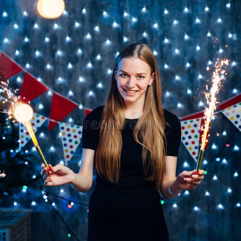 Menina que comemora a véspera de anos novos com luz de bengal Natal fotografia de stock