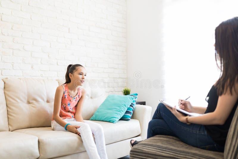 Menina que compartilha de problemas com o psicólogo Sitting On Sofa imagem de stock royalty free