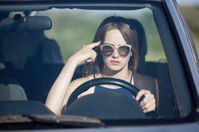 Menina que conduz um carro com um dedo perto de seu templo imagens de stock